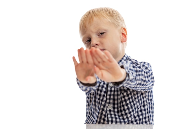 A boy in a blue plaid shirt put his hands forward. isolated on white wall. space for text.