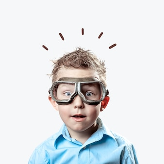 Boy in blue shirt and pilot glasses on light background