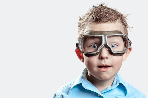Boy in blue shirt and pilot glasses on light