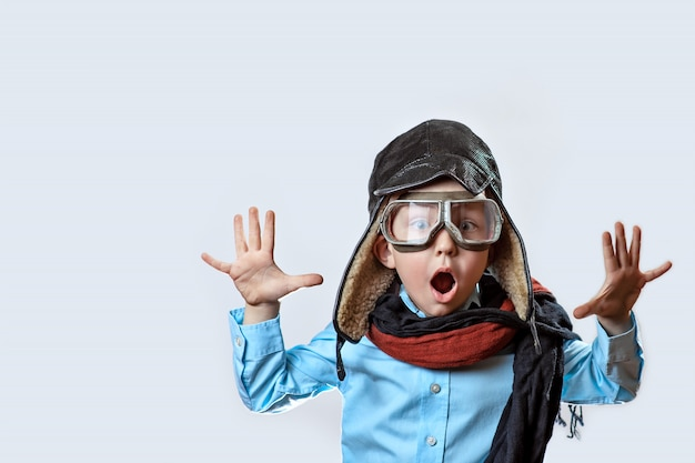 Boy in a blue shirt, pilot's glasses, hat and scarf raised his hands on a light background