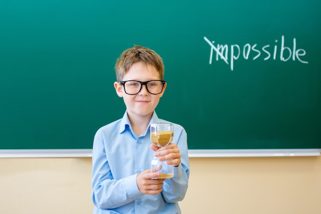 A boy in a blue shirt stands at a blackboard that says impossible he is holding an hourglass in his hand the concept that everything is possible