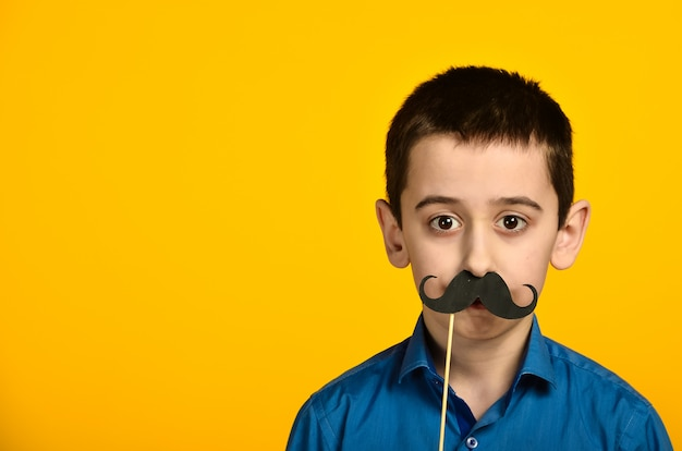 A boy in a blue shirt on a yellow background is twisted and dresses his mustache