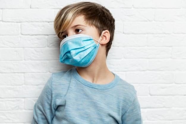 A boy in a blue sweater in a medical mask stands against a white brick wall
