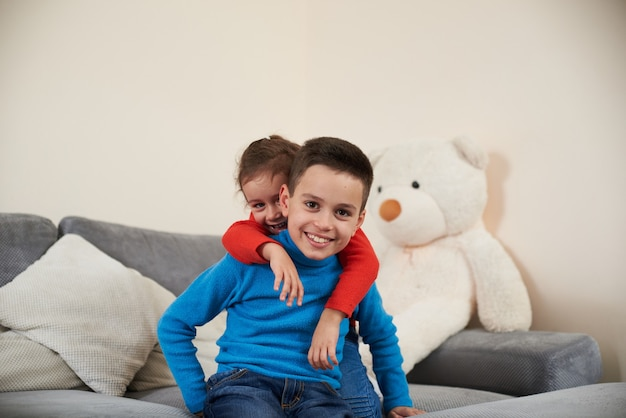 A boy in a blue sweater sits on the sofa while his sister huging him from behind his back and smiling to camera