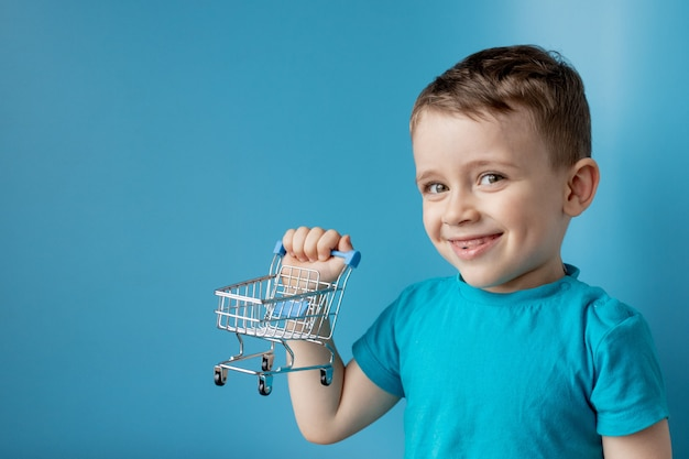 Boy in blue t-shirt is holding little cart for buying goods, products on blue background. shopping and sale concept