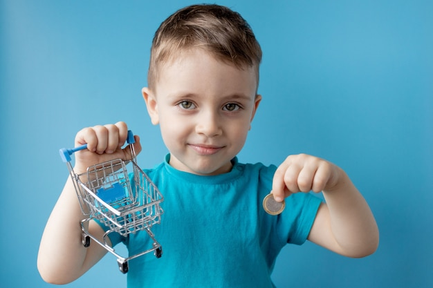 Boy in blue t-shirt is holding shopping cart and coin on blue background. shopping and sale concept.