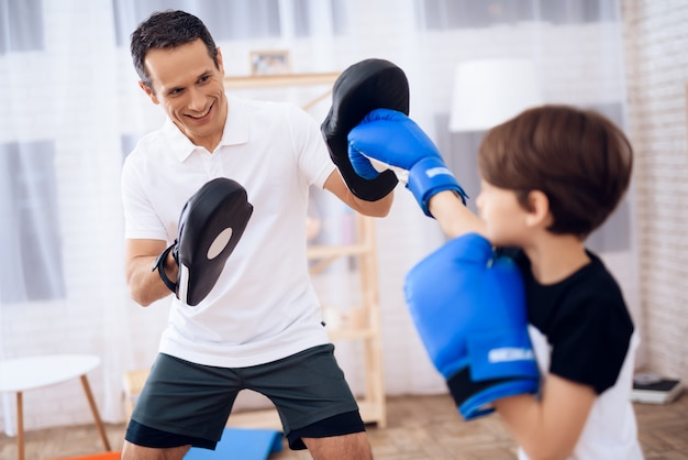 Boy in boxing gloves and man trainer in apartment.
