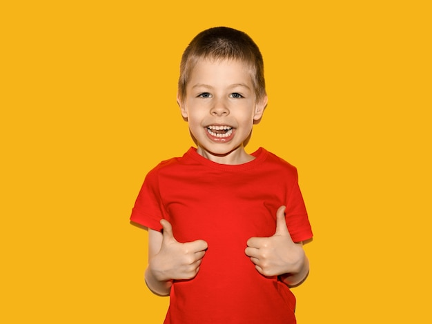 Boy in a bright red tshirt very cheerful smiling and showing thumbs up