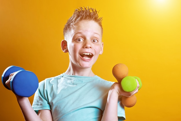 A boy in a bright t-shirt with dumbbells on a yellow