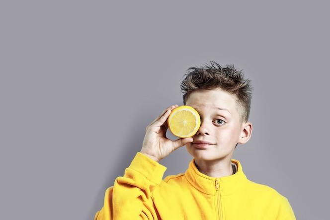 一件明亮的黄色夹克的一个男孩用柠檬在他的在蓝色背景的手上