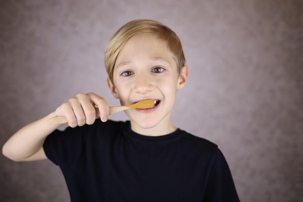 Мальчик чистит зубы эко-щеткой из натурального материала