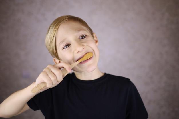 Мальчик чистит зубы, держа эко-щетку из дерева
