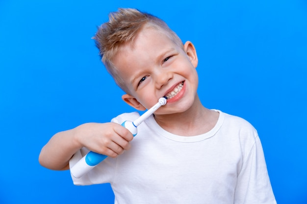 Boy brushing teeth with electric toothbrush on blue