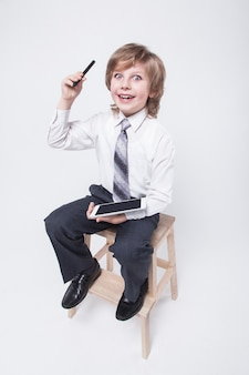 Boy in a business suit and tie holding a tablet