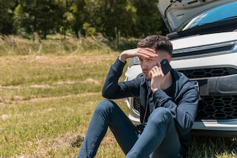 Boy calling next to broken down car