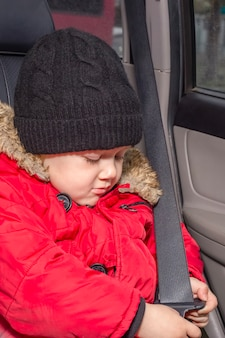 A boy in a car trying to fasten his seat belt.