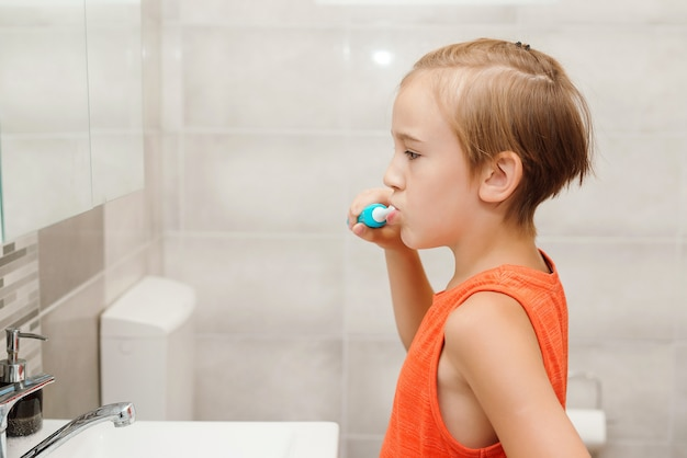 Boy cares about health of his teeth. happy boy cleaning teeth. kid brushing teeth with electic brush in bathroom. dental hygiene every day. health care, childhood and dental hygiene.
