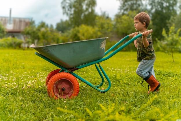 Boy carries a trolley through his garden