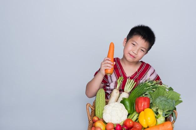 Мальчик с корзиной овощей на сером фоне