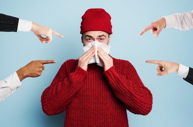 風邪をひいた少年がウイルスに感染したとして告発された。シアンの背景のスタジオ