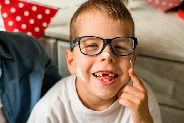 少年は彼の誕生日を祝います。その少年は顔にケーキで覆われている。自宅での家族のお祝い。誕生日パーティーで眼鏡をかけて笑う赤ちゃん