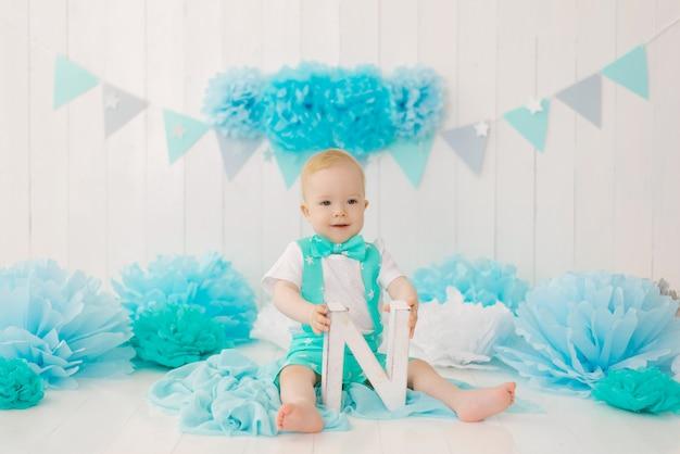 Мальчик празднует свой первый день рождения, держит букву n в руках и улыбается