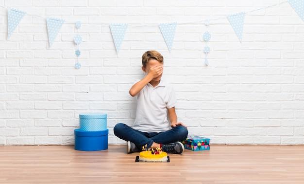 手で目を覆っているケーキで彼の誕生日を祝っている少年