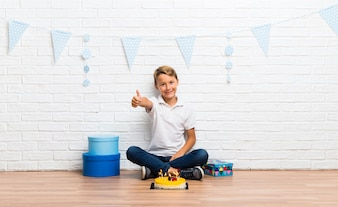 Boy celebrating his birthday with a cake giving a thumbs up gesture and smiling