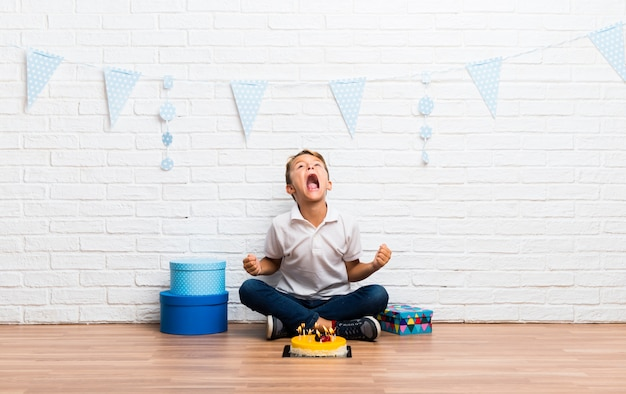 Boy celebrating his birthday with a cake annoyed angry in furious gesture