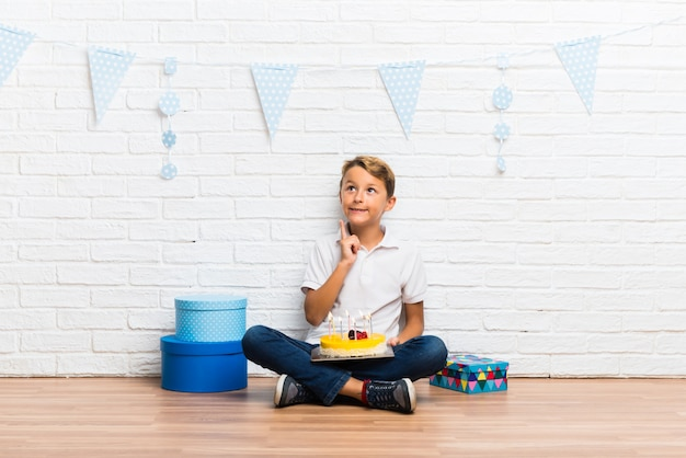 Boy celebrating his birthday with a cake standing and thinking an idea