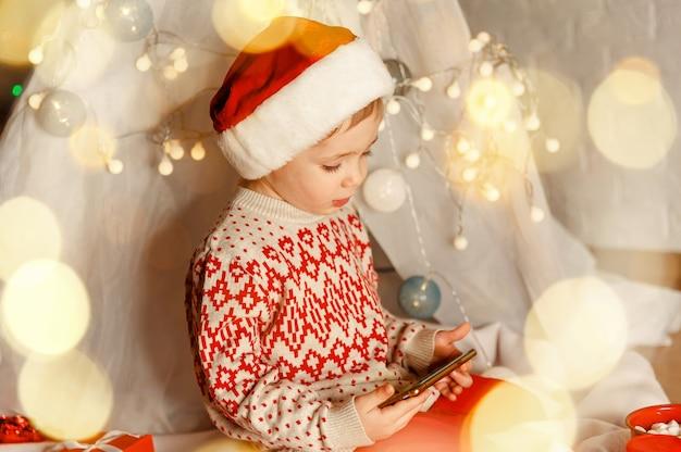 Мальчик болтает с друзьями через видеозвонок во время рождественских праздников