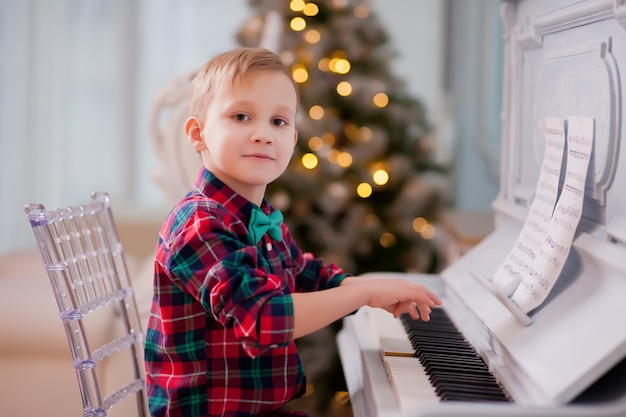 Boy in a checkered shirt and tie butterfly playing piano. christmas concept.