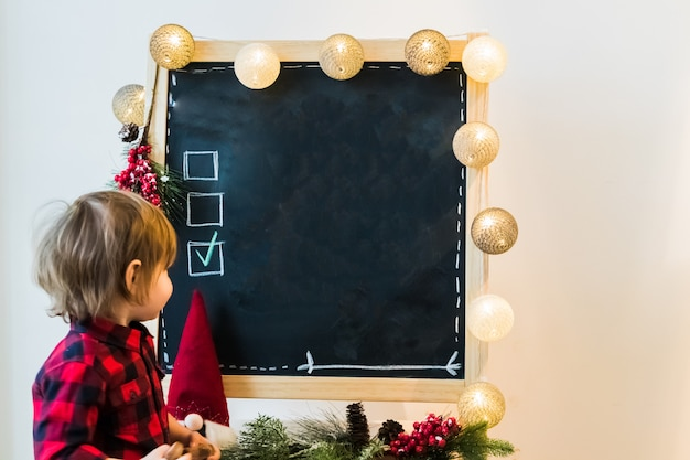 A boy checking options on a blackboard with copyspace