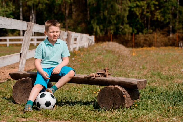 A boy cheerleader sits with a football on the field on the bench watching football.