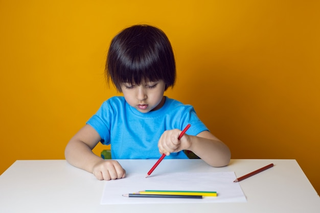 Boy child in a blue t shirt on a yellow wall sits at a white table and draws with colored pencils