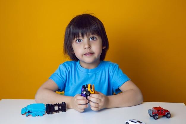 파란색 티셔츠에 소년 아이가 테이블에 앉아 장난감 자동차와 함께 재생