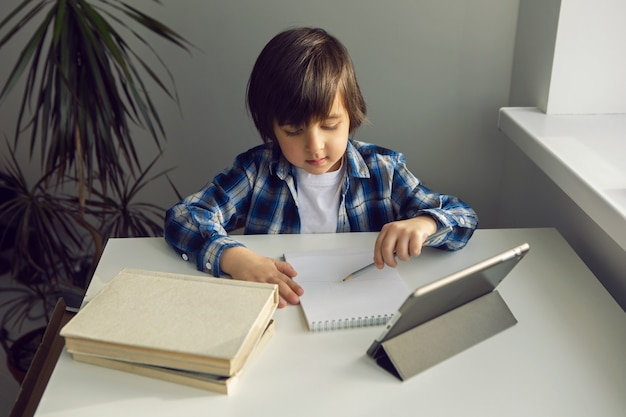 Boy child sits at a desk and learns with a tablet notebook and book