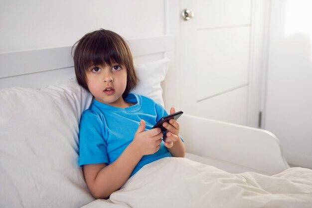 소년 아이는 검은 전화와 담요 아래 침대에 앉아 연극