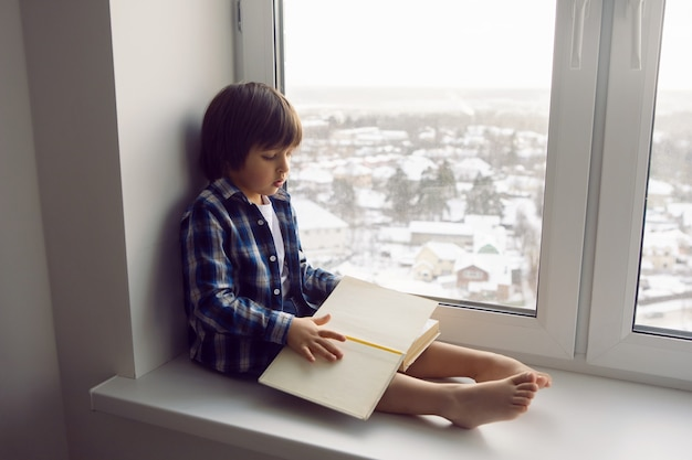 男の子の子供は高層階で冬に本を持って家の窓に座っています