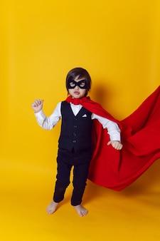 맨발로 노란색 벽에 양복과 검은 마스크 소년 아이 슈퍼 영웅