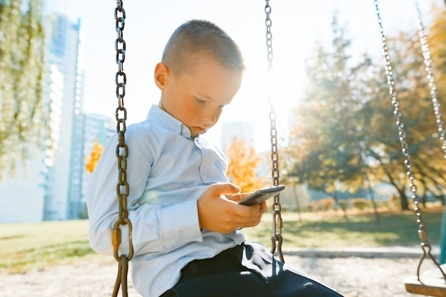 Boy child on a swing in the autumn park