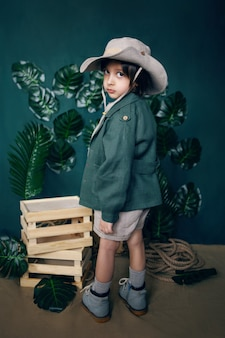 Boy child traveler in a hat stand on wooden boxes in a studio on a green background