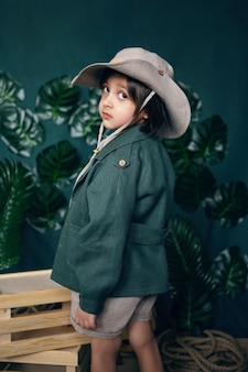 Boy child traveler in a hat stand wooden boxes in a studio on a green background