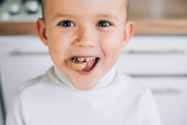 A boy child tries to crack a walnut showing healthy strong baby teeth,makes an effort