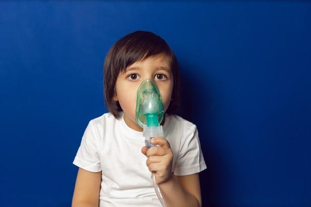 소년 아이가 치료를 받고 어린이 클리닉에서 파란색 벽의 벽에 흡입 녹색 마스크를 호흡합니다.