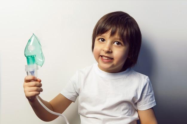 소년 아이가 치료를 받고 어린이 클리닉의 흰 벽 벽에 흡입 녹색 마스크를 호흡합니다.
