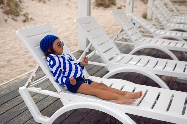 男の子の子供は砂とビーチを歩きます。青い縞模様のジャケットの長椅子に横たわって