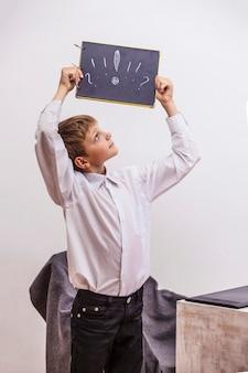 白いシャツのビジネスマンのオフィスで、コンピューターを持った男の子。スタジオ、テクノロジー、モニター、アイデア、コミュニケーション。