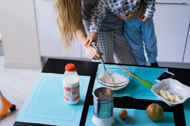 부엌 파이에서 요리하는 엄마와 소년 아이