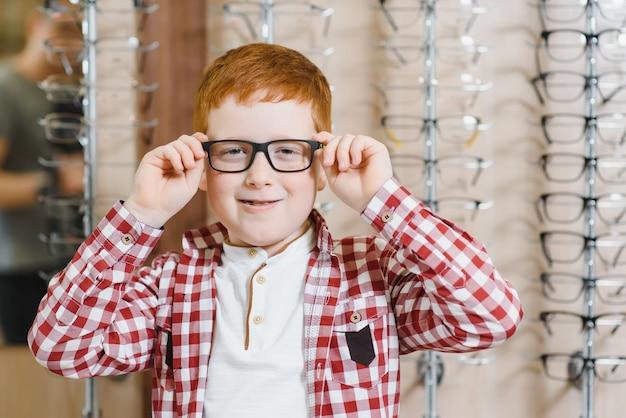 Мальчик выбирает очки в магазине оптики.